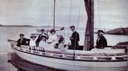 Gammelt bilde av mennesker i seilbåt