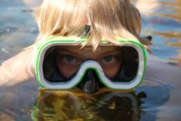 Gutt med dykkermaske i fjæra. Foto: Oslofjordens Friluftsråd.