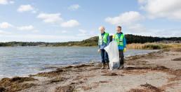 To gutter plukker søppel langs en strand