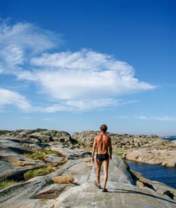 Mann med ryggen til vandrer over svaberg på Kløvningen Færder nasjonalpark