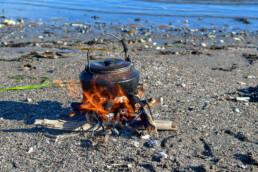 Lite bål på sanden ved vannkanten. Foto: Birgit Brosø
