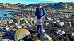 Mann som plukker søppel langs strand